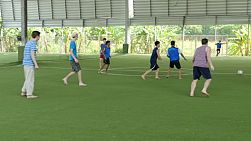 A group of high school students have fun playing a game of soccer against Thai students in Bangkok, Thailand.