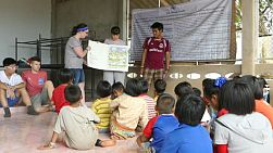 A group of high school students on an overseas missions trip sharing bible stories to kids in a hill tribe village in Chiang Rai, Thailand.