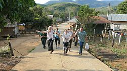 A group of high school students on an overseas missions trip walks up the road singing and dancing visiting while a hill tribe village in Chiang Rai, Thailand.