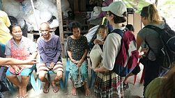 A group of young people on a short-term missions trip hands out bags of rice to elderly people living in the slums of Bangkok, Thailand.