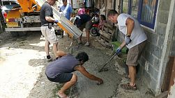 A group of young adults on a short term overseas missions trip have fun pouring fresh cement in the slums in Bangkok, Thailand.