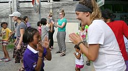 "A young adult on a short term overseas missions trip have fun teaching ""Paddy Cake"" to a Thai girl in the slums in Bangkok, Thailand."