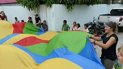 A group of young adults on a short term overseas missions trip have fun using a parachute with Thai children in the slums of Bangkok, Thailand.