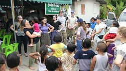 A group of young adults on a short term overseas missions trip have fun teaching action songs to Thai children in the slums in Bangkok, Thailand.