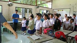 A group of young adults on a short term overseas missions trip have fun teaching action songs to Thai children during English class in Ratchaburi, Thailand.