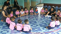 A group of young adults on a short term overseas missions trip oversee a lesson to kindergarten students in Ratchaburi, Thailand.