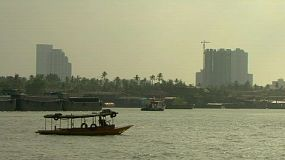 A river boat taxi passes an unloaded barge heading up the Chao Phraya river in Bangkok, Thailand.