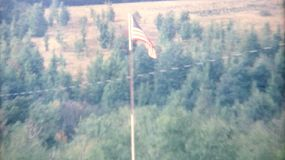 An American flag flies high above a campsite where a family is having a big summer reunion in 1967.