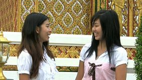 Two Asian girls meet near the temple and start talking only to be interrupted by a cell phone call which ends the conversation.