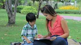 A pretty Thai mother patiently teaches her young son how to read at the park in Bangkok, Thailand.