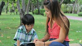 A pretty Thai mother patiently teaches her son to read while spending time together at the park in Bangkok, Thailand.