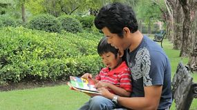 A loving father reads his cute Asian son a book while spending time together at the park.
