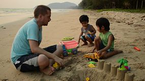 Two cute Asian boys spend time with their dad playing at the beach in Thailand.