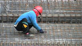 An Asian construction worker ties down rebar in preparation for concrete pouring for an office building in Bangkok, Thailand.