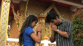 "An attractive Thai man and woman greet each other using the Thai ""wai"" outside the Buddhist temple."
