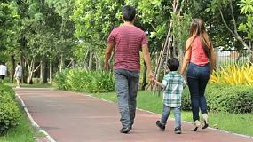 A lovely Asian family leaves the park after spending time together in Bangkok, Thailand.