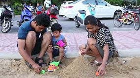 A beautiful Asian family plays together in the sand box at a local playground in Bangkok, Thailand.