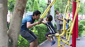 An Asian father and his cute little boy exercise at the local park in Bangkok, Thailand.