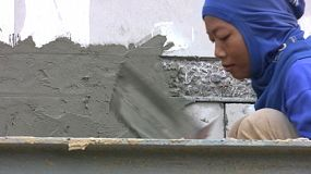 A pretty hard working Asian female construction worker uses her trowel to smooth cement on the side of a new office building in Hua Hin, Thailand.