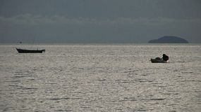 A Thai fisherman slowly paddles his boat towards shore in the Gulf of Thailand, near Sattahip.