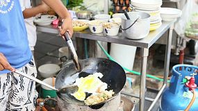A Thai food vendor makes a delicious omelette filled with lots of goodies in Bangkok, Thailand.