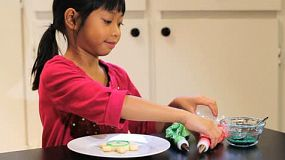 A cute little 6 year old Asian girl adds yummy red icing to her pretty Christmas cookie.