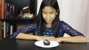 A cute twelve year old Asian girl is excited to have whip cream and sprinkles on her chocolate birthday cupcake.