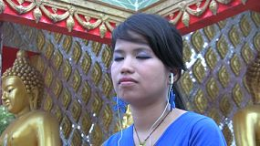 An attractive young Thai girl listens to music outside the temple in Bangkok, Thailand.