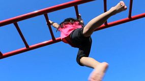 A cute little Asian girl climbs successfully across the monkey bars at the school playground.