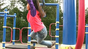 A young Thai girl enjoys hanging out on the school playground equipment doing the rings.