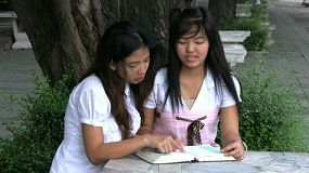 Two Asian university students get together to read the bible and discuss religious concepts.