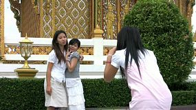 Three pretty Asian girls goof around in front of the temple taking pictures in Bangkok, Thailand.