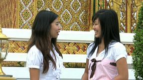 Two Thai girls meet up outside the temple to chat and share a laugh together in Bangkok, Thailand.