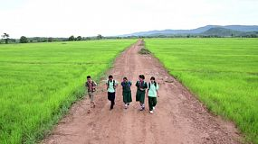 CHIANG RAI, THAILAND, SEPTEMBER 2013: A group of high school aged Asian students walk down road near rice field on the way to school in Chiang Rai, Thailand.