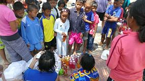 A group of high school students on an overseas missions trip serve lunch during a special kids camp at the beach for Thai and Khmer kids living in the slums of Pattaya, Thailand.