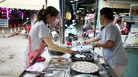 "Thai ladies making the delicious Thai dessert, ""Kanom Krok"" or Coconut Pudding at the market in Bangkok, Thailand."