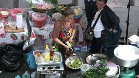 An Asian lady makes delicious Thai food on the sidewalk in downtown Bangkok, Thailand.