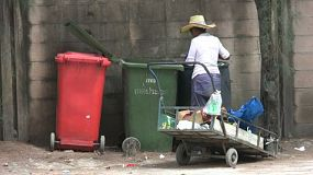 A desperate Asian lady goes through the garbage looking for food and valuables on the streets of Bangkok, Thailand.