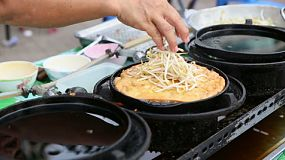 A Thai lady makes a creatively delicious egg omelet on the streets of Bangkok, Thailand.