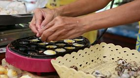 "A Thai lady makes yummy ""Khai Nok Kra Ta"", or Quail Eggs at the market in Bangkok, Thailand."