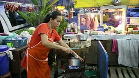 A Thai street food vendor is busy making a tasty spicy soup at the market in Bangkok, Thailand.