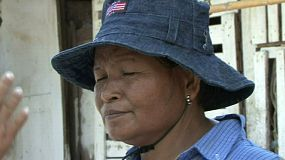 A close up shot of a Thai lady wearing a blue hat showing off her beautiful smile.