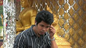 An attractive Thai man sits outside the temple and listens to some music in Bangkok, Thailand.