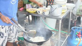 A Thai street food vendor makes a delicious egg omelette at the market in Bangkok, Thailand.