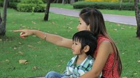 A pretty Thai mother enjoys spending time with her son and exploring new things at the park in Bangkok, Thailand.