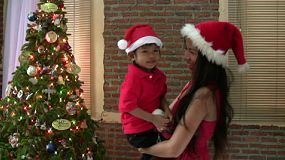 A beautiful Asian mother cuddles and hugs her adorable son in front of the Christmas tree during the holidays.