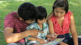 A beautiful Asian family spends time reading to their son in the park in Bangkok, Thailand.