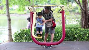 An Asian mom and her cute little boy spent time trying out the exercise equipment at the local park in Bangkok, Thailand.