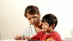 Young Asian mother reading a book together with her young son.