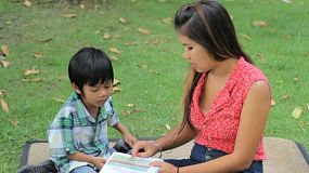 A pretty Thai mother patiently teaching her son to read while spending time together at the park in Bangkok, Thailand.